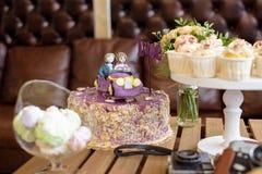 Bolo de casamento, o par no carro, com AMOR do chapéu de coco, close up, queques do casamento Imagem de Stock