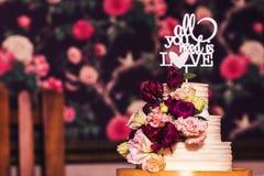 bolo de casamento Três-estratificado decorado com flores bonitas e inscrição de madeira Imagem de Stock Royalty Free