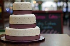 Bolo de casamento a três níveis de Borgonha branca com as pérolas do teste padrão e da prata Foto de Stock