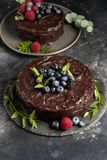 Bolo de chocolate com bagas e as folhas verdes na placa cinzenta fotos de stock