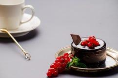 Bolo de chocolate com corinto vermelho em um fundo cinzento Foto de Stock