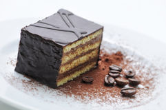 Bolo de chocolate com os feijões de café na placa branca, sobremesa doce, pastelaria, loja, pó de cacau Imagem de Stock