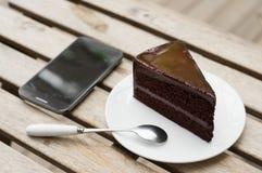 Bolo de chocolate com telefone celular na tabela Imagens de Stock Royalty Free