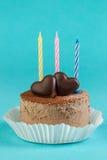 Bolo de chocolate com uma vela em um fundo brilhante Fotos de Stock Royalty Free