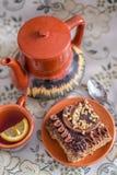 Bolo de chocolate delicioso e doce com creme e porcas e um  de Ñ acima do chá preto com limão grupo de chá com bule, pires e  d imagem de stock