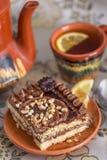Bolo de chocolate delicioso e doce com creme e porcas e um  de Ñ acima do chá preto com limão grupo de chá com bule, pires e  d fotos de stock
