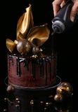 Bolo de chocolate extravagante, fundo preto A mão do th Imagens de Stock