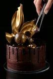 Bolo de chocolate extravagante, fundo preto A mão do th Imagens de Stock Royalty Free