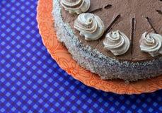 Bolo de chocolate na placa alaranjada no fundo azul Imagem de Stock