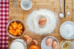 Bolo de cozimento na cozinha - ingredientes da receita da massa com fruto na tabela de madeira, fundo para a pastelaria Fotos de Stock Royalty Free