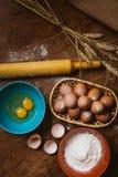 Bolo de cozimento na cozinha rural - ovos dos ingredientes da receita da massa, farinha, açúcar na tabela de madeira do vintage d Imagens de Stock