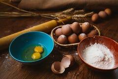 Bolo de cozimento na cozinha rural - ovos dos ingredientes da receita da massa, farinha, açúcar na tabela de madeira do vintage d Imagens de Stock Royalty Free