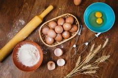 Bolo de cozimento na cozinha rural - ovos dos ingredientes da receita da massa, farinha, açúcar na tabela de madeira do vintage d Imagem de Stock