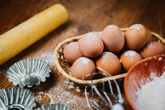 Bolo de cozimento na cozinha rural - ovos dos ingredientes da receita da massa, farinha, açúcar na tabela de madeira do vintage d Fotografia de Stock Royalty Free