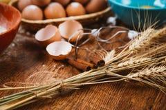 Bolo de cozimento na cozinha rural - ovos dos ingredientes da receita da massa, farinha, açúcar na tabela de madeira do vintage d Foto de Stock Royalty Free