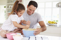 Bolo de And Daughter Baking do pai na cozinha foto de stock royalty free