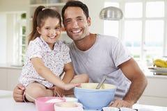 Bolo de And Daughter Baking do pai na cozinha imagens de stock