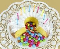 Bolo de esponja circular e confeitos cobertos de açúcar cor-variados do chocolate Fotos de Stock