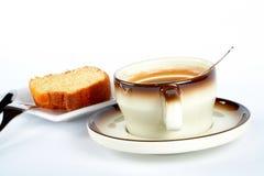 Bolo de esponja com a chávena de café, a colher, a faca e a forquilha na placa cerâmica branca Fotos de Stock Royalty Free