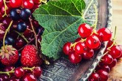 Bolo de esponja da passa de Corinto vermelha Placa com as bagas sortidos do verão, framboesas, morangos, cerejas, corintos, grose Fotografia de Stock Royalty Free