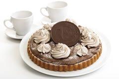 Bolo de esponja do chocolate com a euro- moeda do chocolate, dois copos de café no fundo Foto de Stock