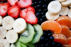 Bolo de esponja do verão com as bananas, as morangos, os corintos, as tangerinas, as uvas-do-monte e o quivi Vista superior horiz fotografia de stock