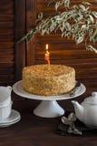 Bolo de mel, copos de chá, bule e flor na tabela de madeira marrom Tempo do chá Imagem de Stock