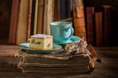 Bolo de queijo caseiro e café no livro velho na biblioteca imagens de stock royalty free