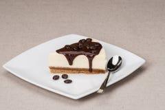 Bolo de queijo com molho de chocolate na placa branca imagens de stock royalty free