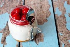 Bolo de queijo da cereja no frasco de pedreiro com a colher na madeira rústica Imagem de Stock Royalty Free