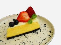 Bolo de queijo delicioso com bagas e a morango frescas no isolado da placa no fundo branco imagem de stock