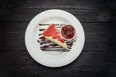 Bolo de queijo delicioso com bagas em uma placa branca sobre a tabela de madeira escura Fotografia de Stock Royalty Free