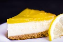 Bolo de queijo do limão no fundo preto decorado com fim do entusiasmo de limão acima fotos de stock royalty free