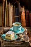 Bolo de queijo e café doces no livro na biblioteca imagens de stock