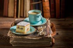 Bolo de queijo e café rústicos no livro na biblioteca foto de stock royalty free
