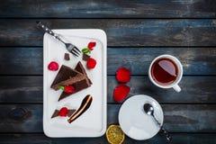 Bolo delicioso da brownie com um copo das pétalas cor-de-rosa e das forquilhas do chá em uma placa branca Vista superior Fundo de Fotografia de Stock