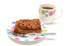 Bolo delicioso da noz na placa e na xícara de café coloridas. Fundo branco imagem de stock royalty free