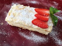 Bolo delicioso de Napoleon com morangos e a hortelã frescas fotografia de stock royalty free