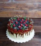 Bolo delicioso do gotejamento da cor do chocolate com bagas Foto de Stock