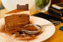 Bolo do crepe do chocolate com chocolate pulverizado no prato branco no th Imagens de Stock Royalty Free