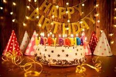 Bolo do feliz aniversario com velas no fundo das festões a fotos de stock royalty free