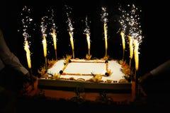 Bolo do fruto do aniversário com velas dos fogos-de-artifício foto de stock