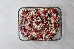 Bolo do pudim de chocolate com cerejas, fatias da amêndoa e biscoitos fotos de stock