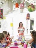 Bolo do serviço da mulher às crianças na festa de anos Fotografia de Stock