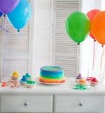 Bolo e queques do arco-íris na festa de anos Imagens de Stock Royalty Free