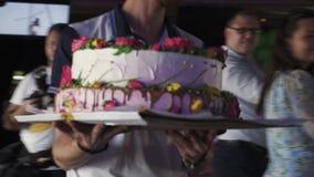 Bolo enorme da posse do garçom com as flores no café celebration evento doces feriado filme