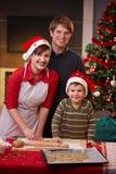 Bolo feliz do Natal do cozimento da família junto Imagem de Stock
