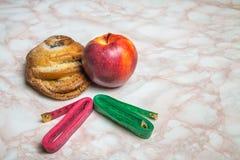 Bolo, maçã e duas fitas de medição Conceito saudável e insalubre do alimento fotografia de stock