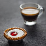 Bolo pequeno da cereja com um vidro do café fresco Fotografia de Stock Royalty Free