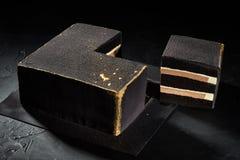 Bolo quadrado preto com bordas do ouro Fundo escuro A vista da parte superior imagem de stock